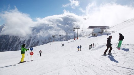 Skiers stand near ropeway station in sunny weather