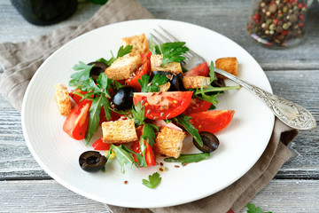 Delicious salad with olives, arugula and tomatoes