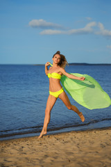 Woman at the beach holding sarong up in the air