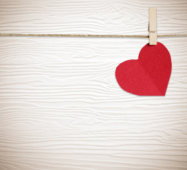 Red fabric heart hanging on clothesline over white wood