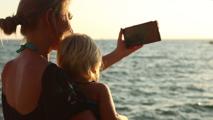 closeup of young blonde mother takes selfie photograph with her
