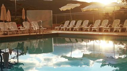 Luxury resort evening time. Pool worker folding sun umbrellas
