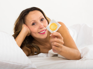 Adult woman holding condom in bed