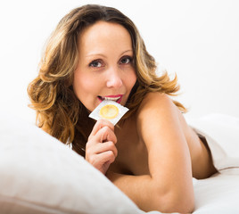 Sexy woman with condom in bed