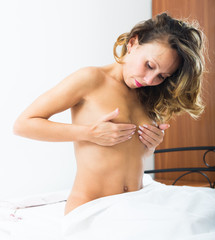 Nude woman covering bosom with hands