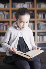 Niña enfrascada en lectura de libro