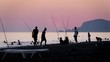 Detaily fotografie Fishermen fish in evening at sunset near floating children, time lapse