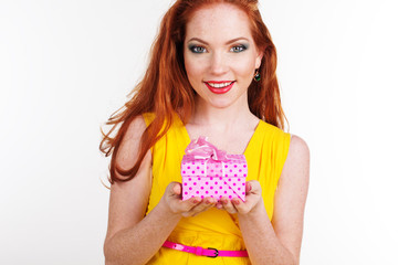 Beautiful redheaded girl is holding gift box