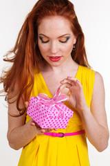 Beautiful redheaded girl is holding birthday gift