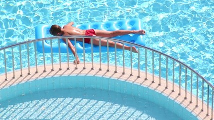Boy lies on mattress in pool holding ledge between pools
