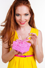 Beautiful redheaded girl is holding gift