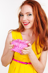 Beautiful redheaded happy girl is holding gift box
