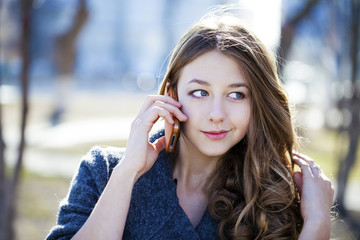 Happy beautiful girl calling by phone