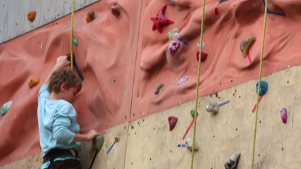 Boy-beginner tries to cross relief part of rock-climbing wall