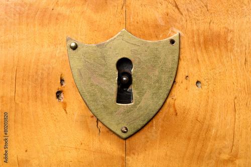 Leinwandbild Motiv Antique shield-shaped lock on bright cherry wood