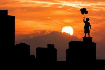 silhouette of boy and building on sunset background