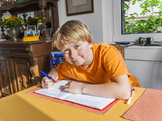 cute pupil writes in a book and prepares homework