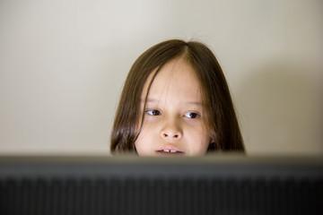 Young girl looking at computer screen