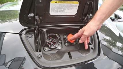 Man closes the lid electromobile Nissan Leaf at the presentation
