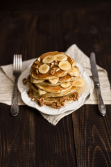 Stack of pancakes with honey,banana and walnuts