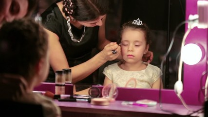 Mother makes makeup to little daughter reflected in mirror