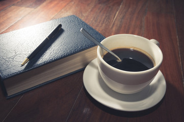 Coffee cup with book and pen