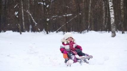 Father ride daughter on a sled through the wall of snow