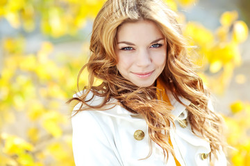 Beautiful woman in a yellow sweater in autumn park