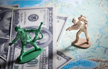 Soldier toys on money and map.