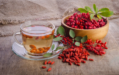 goji fresh antioxidant tea in glass cup and barberries in wooden