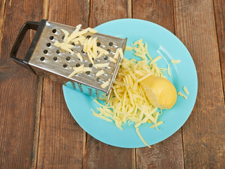 Grated cheese and grater on a plate on the table