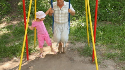 girl in pink suit swings grandfather on children swing
