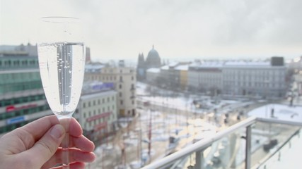 Hand holds glass with mineral water at background of square