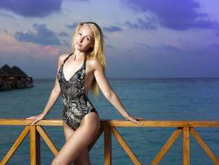 attractive woman standing in bathing suit against sea. Maldives.