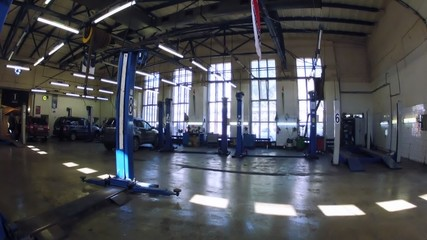 Cars stand in car-care center near big windows, time lapse