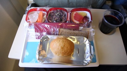 Tray of food: salad, fruit, bread, drink on the plane.