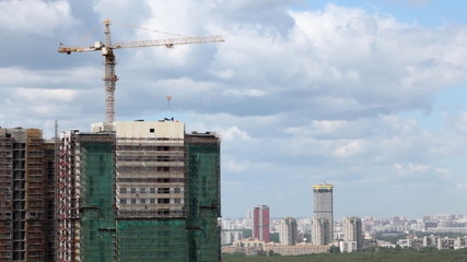 multi-storey building under construction against city landscape with skyscrapers greens and sky