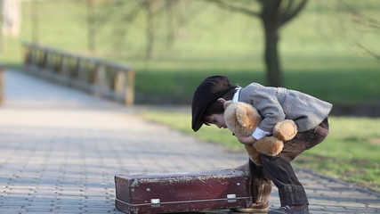 Adorable little boy with suitcase and teddy bear