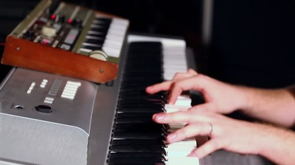 Hand of man which plays on synthesizer in dark studio