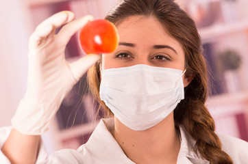 young beautiful woman biologist experimenting with tomato