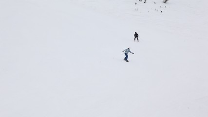 Skier and snowboarder go on mountain slope downwards mountain
