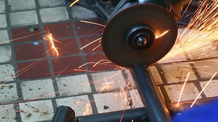 Whirling angle grinder cutting off pieces of water metal pipe