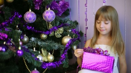 Little girl with gift box looks at snowflake near Christmas tree