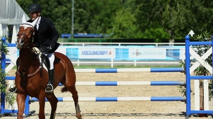Horseman on horse jumps over barrier at competitions