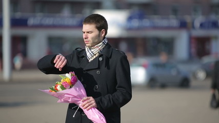 A man with flowers waiting for his woman in the city