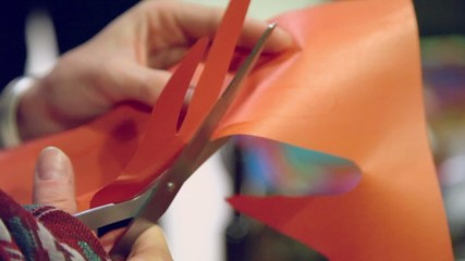 Hands cut out contour of palm by scissors from orange paper