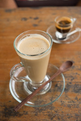 coffee latte in tall glass with wooden spoon