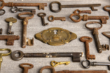 Brass lock surrounded by rusty antiques keys