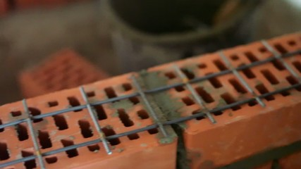 Metalware lattice on brick wall under construction, closeup