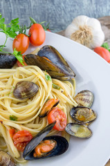 Pasta with mussels, clams and cherry tomatoes on wooden table